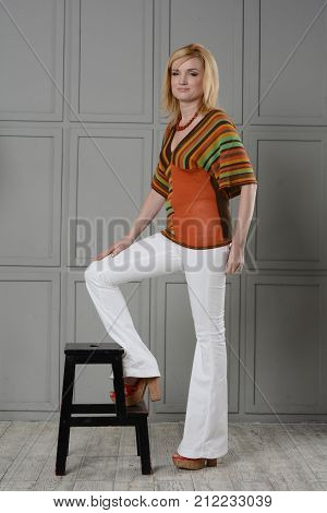 A beautiful girl stands near a tall black stool. She is dressed in a striped knitted blouse and white jeans, high-heeled sandals in the style of the 1970s. One hand lies on the hip. Unusual background.