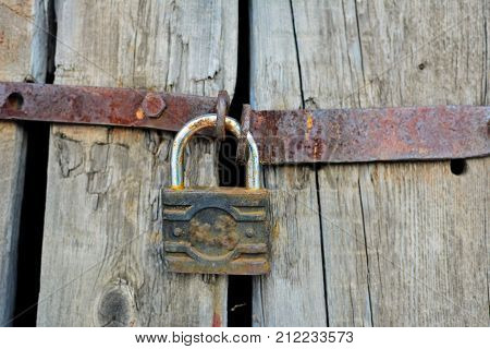 Old rusty padlock on a decaying fence. Security concept: open padlock on wooden wall.