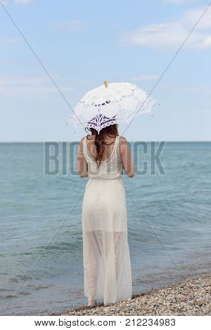 redhead woman with umbrella at the beach