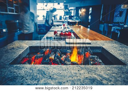 Restaurant kitchen interior: brazier with burning wood, made of natural stone with fire for BBQ. In the background two chefs working prepearing delicious food. Bright blue color filter toning