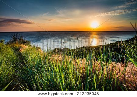 Sunset sky background. Natural Sunset Sunrise Over Ocean. Bright Dramatic Sky And Blue Water. Colorful Nature Landscape. View From The Beach With Green Grass.