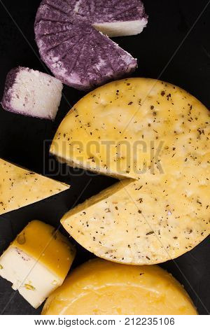 Assortment of dairy handmade milk products, top view. Quality sorts of winery cheese and Caciotta with herbs and pistachio, traditional cuisine and healthy food concept