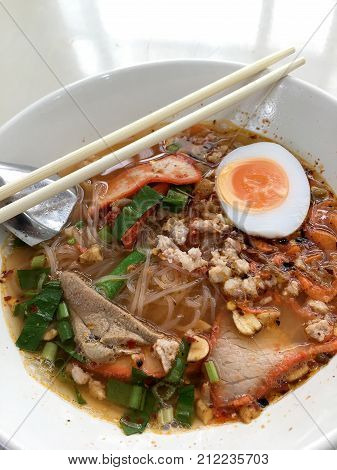 Thai Style Spicy Soup And Noodle With Pork And Lemongrass, Chilly Pasted And Lime Juice In White Blo