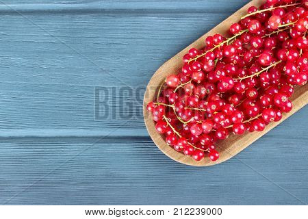 Ripe redcurrants in a wooden plate on a rustic wooden background copy space.