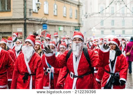 Stockholm, Sweden – December 11, 2016: Hapy People Dressed Up As Santas Run Through The Old Town Of