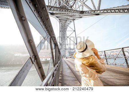 Young woman in hat enjoying beautiful view standing on the famous iron bridge during the foggy and windy weather in Porto, Portugal