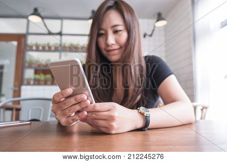 Closeup image of a beautiful Asian woman holding and using smart phone in modern cafe