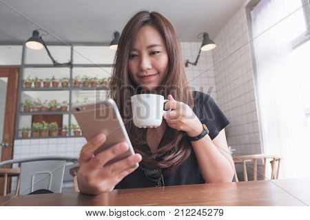 Closeup image of a beautiful Asian woman holding and using smart phone while drinking hot coffee on wooden table in modern cafe