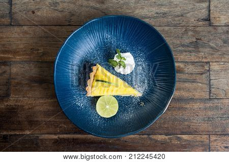 Top view image of a yellow lemon curd cake in blue ceramic plate on wooden table