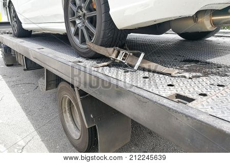Car Tire Secured With Safety Belt On Flatbed Tow Truck