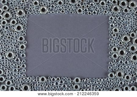 A Bunch Of Screw Nuts On A Gray Background