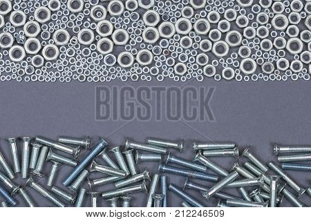 A Bunch Of Screw Nuts And Bolts On A Gray Background
