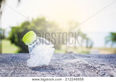 Plastic bottle was pressed use for recycle in out door park background.