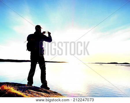 Man In Waterproof Jacket On Rocky Coastline  Takes Photo  By Smart Phone. End Of Marvelous Day