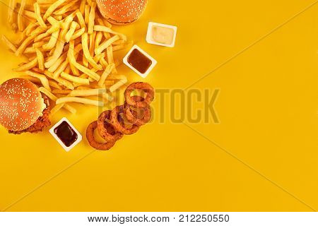 Fast food concept with greasy fried restaurant take out as onion rings, burger, fried chicken and french fries as a symbol of diet temptation resulting in unhealthy nutrition. On yellow background. Top view. Copy space. Still life. Flat lay.