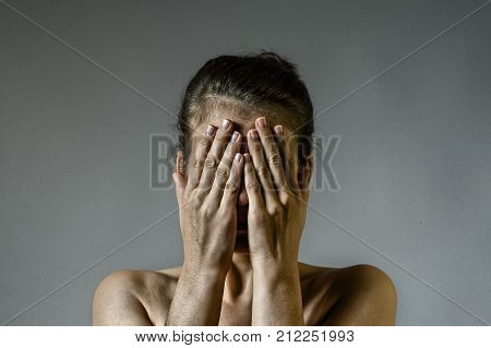 Concept of fear shame domestic violence. Woman covers her face her hands on scratched background.