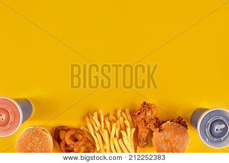 Fast food dish on yellow background. Fast food set fried chicken, meat burger and french fries. Take away fast food. Top view. Copy space. Still life. Flat lay.