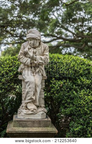 Sydney Australia - March 23 2017: Sweep Boy white marble statue presenting cold and sad youngster a figure out of Donizetti opera 'Linda da Chamonix' in Royal Botanical Garden. Green tree background.