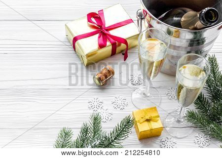 Champagne for celebrate new year. Glasses, bottle in bucket, spruce branch on white wooden background.