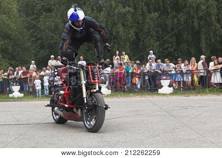 Verkhovazhye, Vologda region, Russia - August 9, 2014: Stunts on a motorcycle by Aleksey Kalinin. Alexei Kalinin professional stantrayder. Champion of the Baltic States in 2005 Bronze medalist of the Baltic States in 2006 bronze medalist MOTUL M1 - Stunt