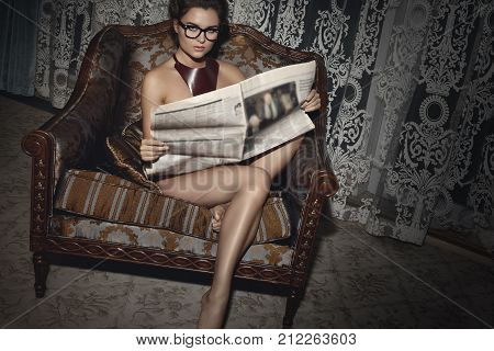 Woman Sitting In Armchair With Newspaper