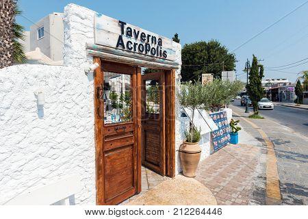 FALIRAKI, GREECE - AUGUST 2017: Wooden doors in white arch as tavern entrance decoration. Rhodes island, Greece.