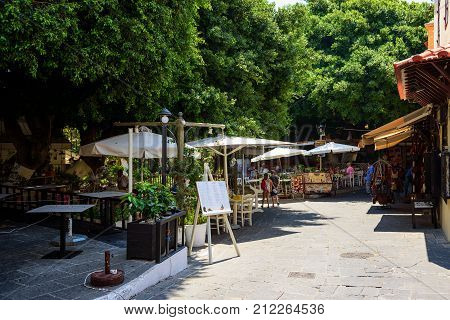 RHODES, GREECE - AUGUST 2017: Street with small taverns and souvenir shops in Rhodes town. Rhodes island, Greece