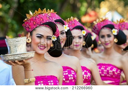 Denpasar Bali island Indonesia - June 10 2017: Group of beautiful women in traditional Balinese costumes carry religious offering for hindu ceremony on street parade at art and culture festival.