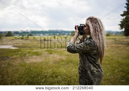 Photographer woman camera photoshoot backstage concept. Working process. Unity with nature.