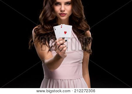 Sexy brunette woman in a chic gently pink dress, holding aces winning hand on a black background. Focus on poker cards in hands. Poker. Victory. Luck