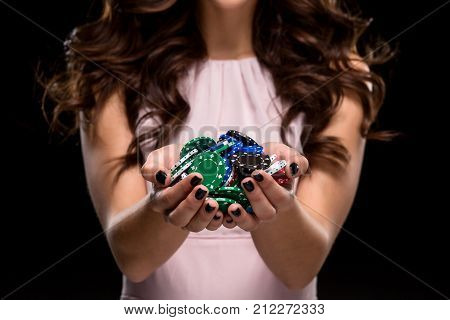Sexy woman in a chic gently pink dress holding colored poker chips on a black background. Woman winning. Casino. Poker. Victory. Luck. Close-up of poker chips