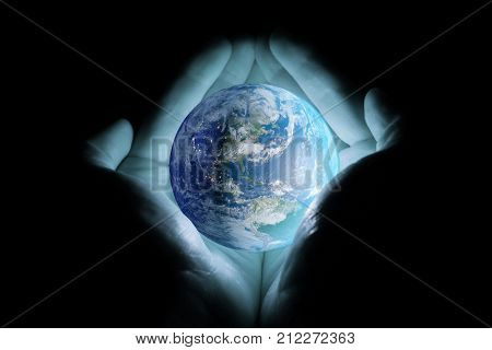 Men's hands holding the planet earth rotated the continents of North and South America with a blue glow on a black background.