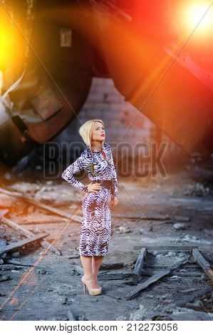 Young elegant blond woman in a stylish leopard print dress high heels stands on ruins of an old factory.