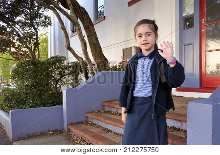Young school girl going to school (girl age 7) and say goodbye. Children education concept