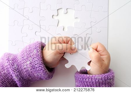 Child hands holds the last puzzle piece of a Jigsaw puzzle. Problem solving concept. Copy space