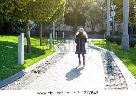 Girl with long blond curly hair in dark blue coat and french beret runs along the path of the autumn city picture from the back.
