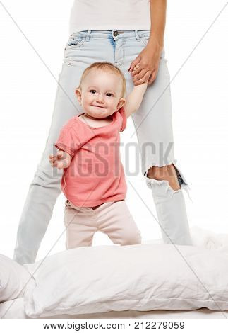 Happy little baby in bed with mother. Mom on the photo just feet with white background
