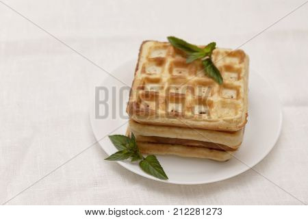 Belgian Waffles With Fresh Mint On A White Plate On A White Tablecloth, Retro Toning, Close-up