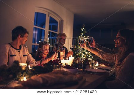 Three generation family enjoying christmas dinner together at home. Extended family toasting wine at christmas dinner.