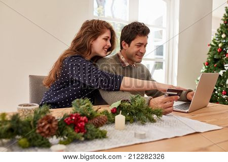 Young family with laptop and credit card buying online christmas and new year gifts. Couple doing online shopping for christmas.