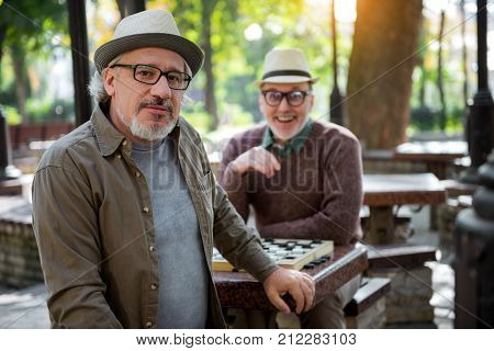 Checkers is my hobby. Portrait of cheerful mature man looking at camera with joy while sitting at table in park. His friend is laughing on background