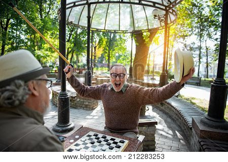 Portrait of excited mature male pensioner winning his opponent in checkers. He is stretching arms up and laughing. Triumph concept