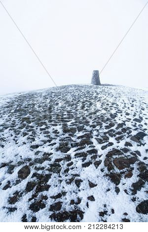Trigonometrical point on the summit of Mam Tor in Winter. Peak District Derbyshire UK