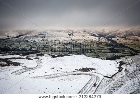 A car drives up a snow covered mountain road in winter. Edale valley Peak District UK