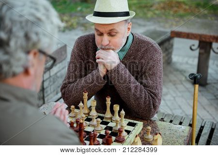 Portrait of pensive mature man looking at chessboard with seriousness. He is sitting opposite his opponent in park