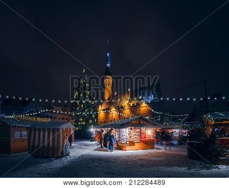 TALLINN, ESTONIA - JANUARY 4, 2017: Christmas fair at the town Hall square in Tallinn. Festive lights and decorated Christmas tree in the old town. Winter Estonia.