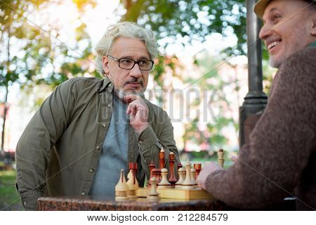 Trying to guess the next move of opponent. Serious old man is looking at his mate pensively while playing chess with him. Cheerful pensioner is smiling