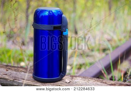 A Blue Thermos For Saving Hot Drinks. Thermos On The Left. Autumn.