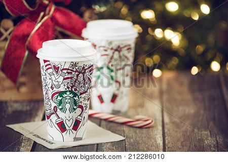 Dallas TX - November 4 2017: Starbucks popular holiday beverage served in the new 2017 designed holiday cups. Displayed with candy cane on wooden rustic table. Sparkling Christmas tree lights background.