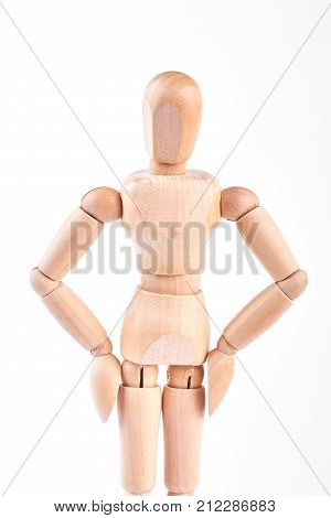 Wooden dummy with hands on hips. Wooden mannequin standing on white background. Wooden human dummy.